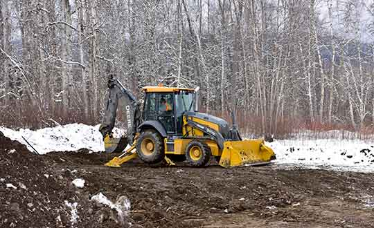 Picture of a student Interior Heavy Equipment Operator operating a Rubber Tire Backhoe
