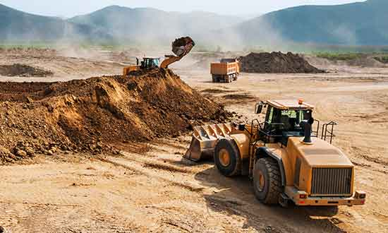 Image of students operating loaders on the job site during Loader training